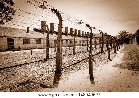 OSWIECIM POLAND - MAY 12 2016: Barbed wire surrounding concentration camp Auschwitz-Birkenau in Oswiecim Poland.