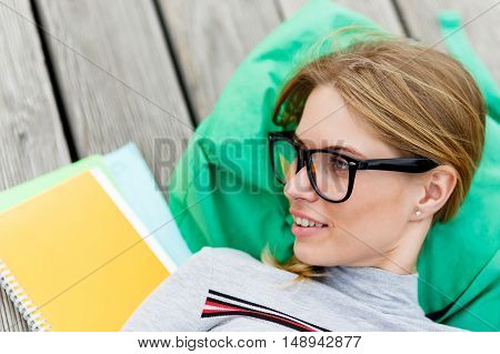 Girl in glasses lying on green backpack. closeup