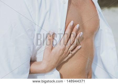 Sexy muscular naked man and female hands unbuckle his jeans.