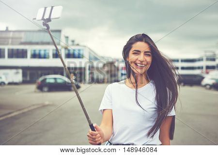 Happy woman with long hair taking a self portrait using a smart phone attached to a selfie stick in the middle of street under cloudy sky