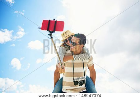 Fun couple or tourists on vacation taking a selfie piggy backing using a stick amd mobile phone against a cloudy blue sky