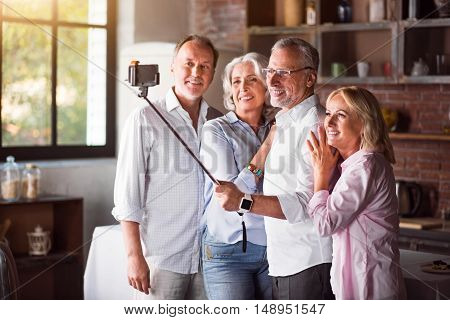Pleasant family in lightcolored clothes using selfie-stick for a photo after lunch in the kitchen