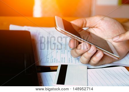 Close up male using mobile phone by card information when shopping online. E-wallet concept.