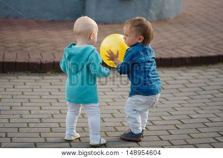 happy little boy and girl playing with yellow ball