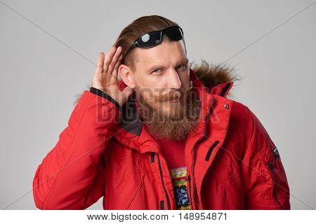 Portrait of a man wearing red winter Alaska jacket with hand on ear listening, studio shot