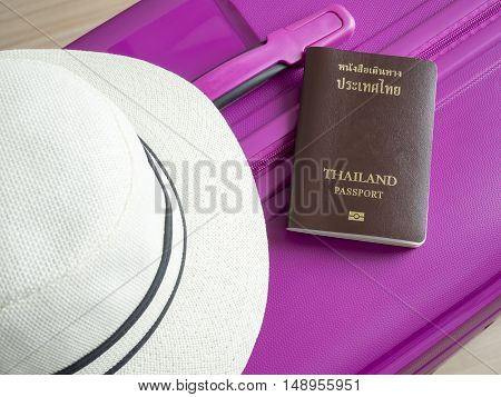 Closeup Thailand passport and white hat on pink suitcase