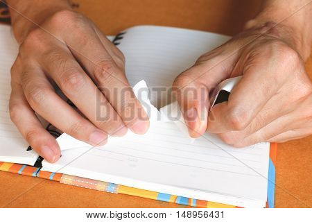 Close up woman hand ripping or tear white paper on notebook