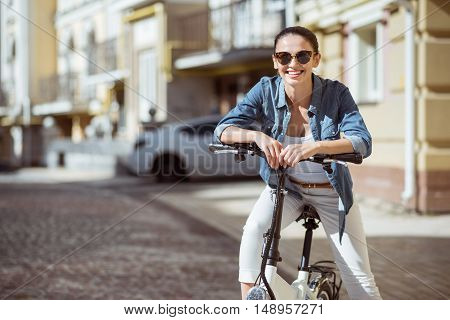 Express positivity. Positive content charming woman smiling and riding a bicycle while expressing joy