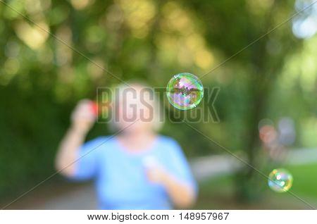 Senior Woman Blowing Iridescent Soap Bubbles