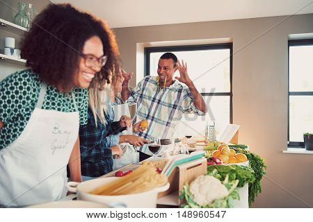 Group of young adults goofing off at table covered with pasta and vegetables for cooking class