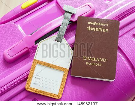Closeup Thailand passport and luggage tag on pink suitcase