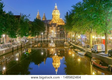 Facades of traditional Dutch houses on the canal in the night light. Red light district. Amsterdam. Netherlands.
