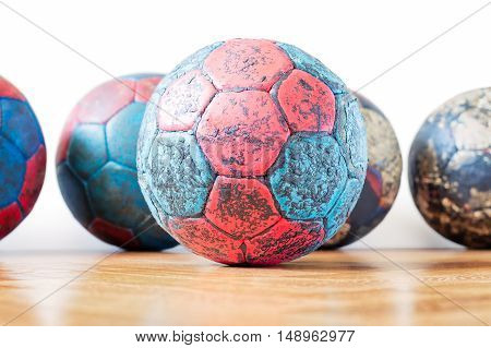 Dirty red and blue handball ball on a wooden parquet floor