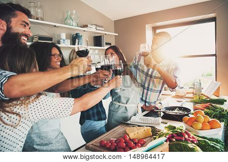 Group of people toasting wine glasses while preparing food for meal at large kitchen counter indoors