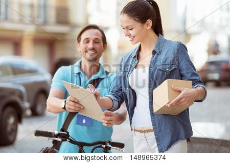 Put it here. Positive professional courier delivering parcel while delighted client signing the paper and holding the box
