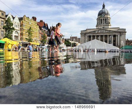 NOTTINGHAM ENGLAND - SEPTEMBER 24: Girls playing in water various market stalls behind in Market Square Nottingham City Centre. In Nottingham England. On 24th September 2016.