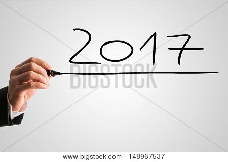 Businessman handwriting the underlined date 2017 with a black marker on a grey background with copy space in a concept of New Year celebrations.