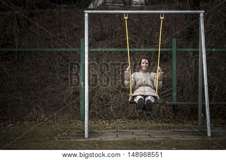 Smiling woman in a warm winter jacket swinging on a swing in a park with her legs extended straight ahead against a dark hedge background with copy space.