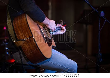 Guy Sitting In A High Chair And Playing Acoustic Guitar