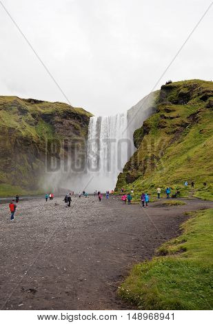 Skogafoss waterfall and tourists in Iceland in July