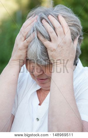 Old age woman holding her head