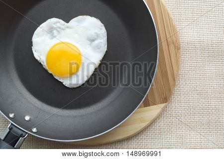 Fried egg in a shape of the heart on the pan. Cutting board and weave cloth under.
