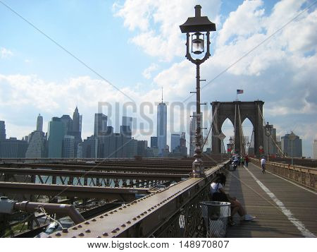 Brooklyn Bridge famous symbol of New York City, USA with downtown Manhattan skyscrapers landscape, sky, clouds people background during sunny summer day. Travel tourism popular destination concept with empty copyspace