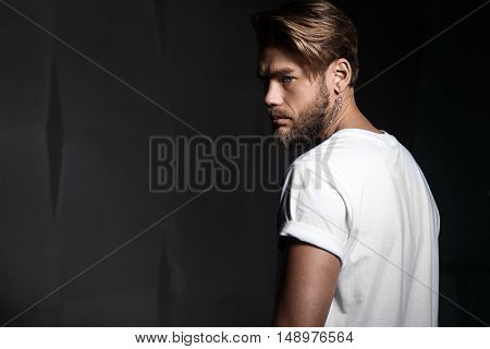 Portrait of a handsome man in a white t-shirt from the back