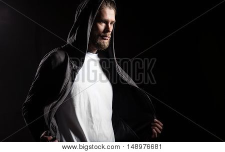 Portrait of a guy in blank t-shirt on a black background
