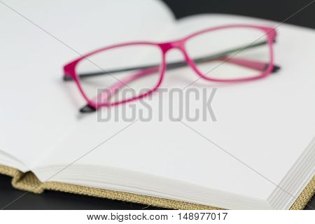 Folded reading glasses on blank book pages with copy space. Only front of book is in focus.