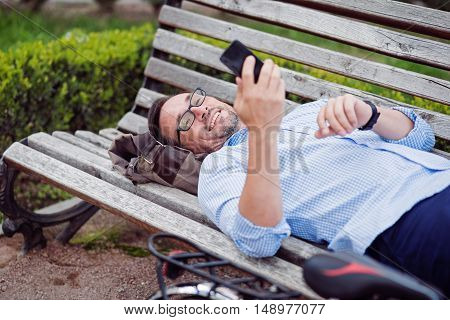 Nice message. Grizzle joyful man using cellphone and smiling while lying on the bench.
