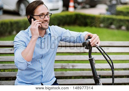 Joyful conversation. Handsome bespectacled man speaking on cellphone and smiling while sitting on the bench.