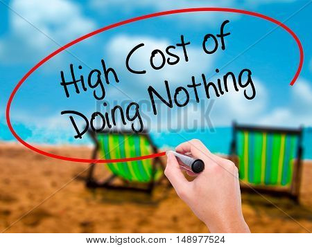 Man Hand Writing High Cost Of Doing Nothing With Black Marker On Visual Screen