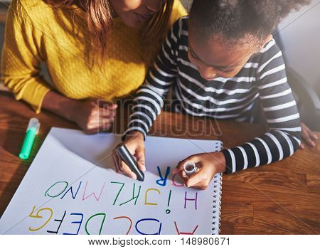 Overhead view of child learning alphabet at home with mother black mother and daughter