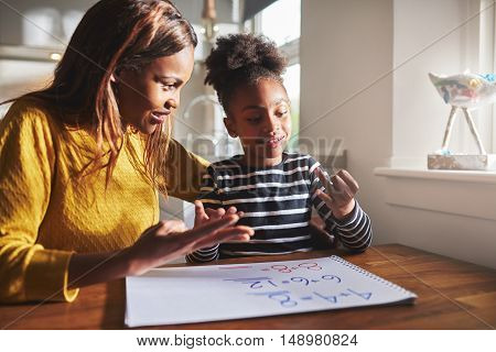 Happy young girl learning to calculate with mother at home black woman and child