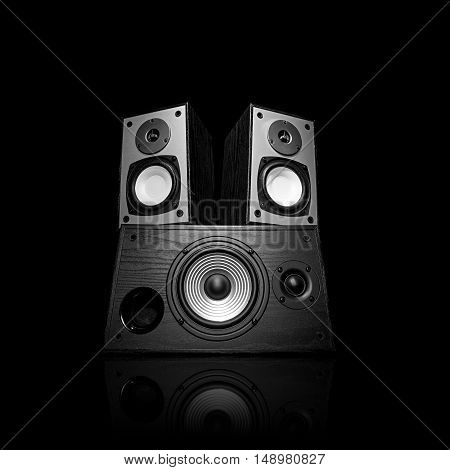 Image of three audio speakers in a wooden case. Photo black and white isolated on a black background with reflection on a horizontal surface. There is an empty seat for your text.