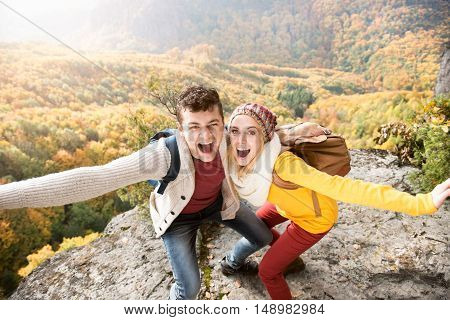 Beautiful couple in autumn nature standing on a rock against colorful autumn forest, posing, arms stretched