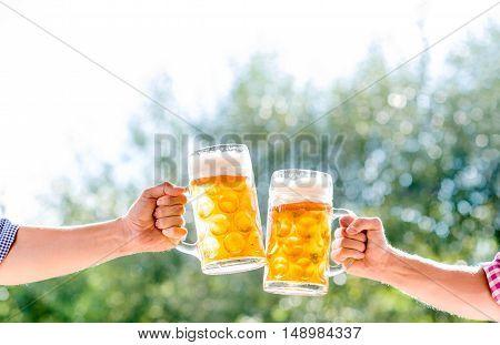 Hands of two unrecognizable men holding mugs of beer, clinking. Oktoberfest. Sunny summer garden.