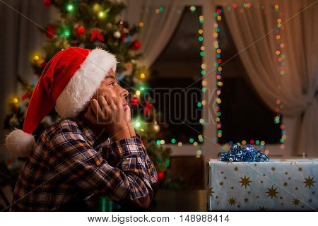 Thoughtful black boy on Christmas. Sad afro kid on Christmas. Too sad for celebration. Cheer up my friend.