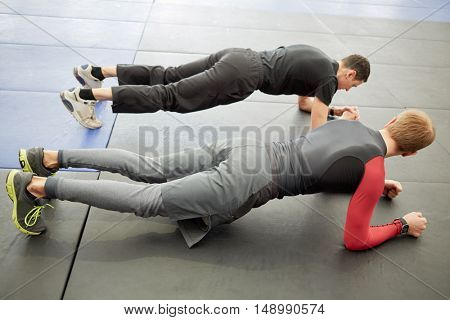 Man and coach do slat exercise on floor in sport club.