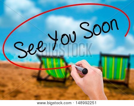 Man Hand Writing See You Soon With Black Marker On Visual Screen.