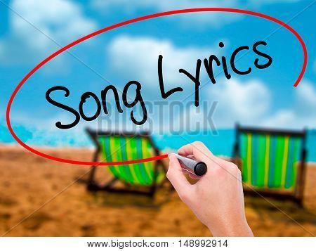 Man Hand Writing Song Lyrics With Black Marker On Visual Screen
