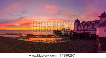 Dramatic sky in yellow red and magenta colors and Penarth Pier before sunrise. Panorama image.