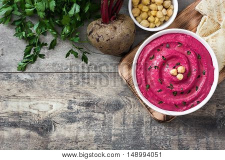 Beet hummus in white bowl on wooden background