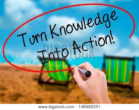 Man Hand Writing Turn Knowledge Into Action! With Black Marker On Visual Screen