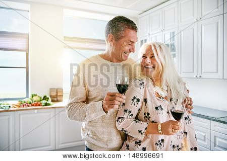 Loving elderly couple enjoying a happy retirement standing arm in arm smiling and laughing as they drink a glass of red wine together in the kitchen