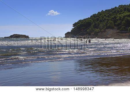 Summertime.Gargano coast:Portonuovo beach (Vieste):bathers enjoying themselves in the waves.Italy,Apulia.