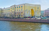 The scenic yellow mansion at the embankment of Griboedov Canal with the giant arch in its corner facade that is slightly concave inward located on Pokrovsky Island St Petersburg Russia. poster