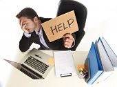 young desperate businessman suffering stress working at office computer desk holding sign asking for help looking tired exhausted and overwhelmed by heavy work load poster