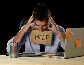 young desperate businessman suffering stress working at office computer desk holding sign asking for help looking tired exhausted and overwhelmed by heavy work load isolated on black background poster